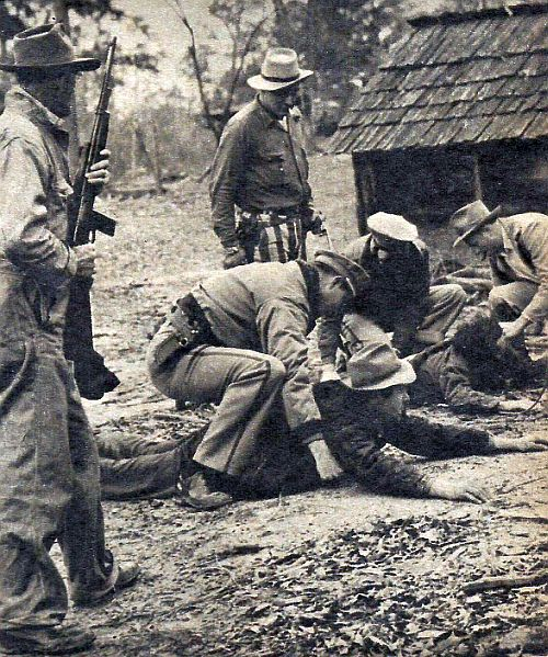 Crippled by a bullet, Leon Turner (foreground, with hat) and Windell White are handcuffed outside the shack where they hid.